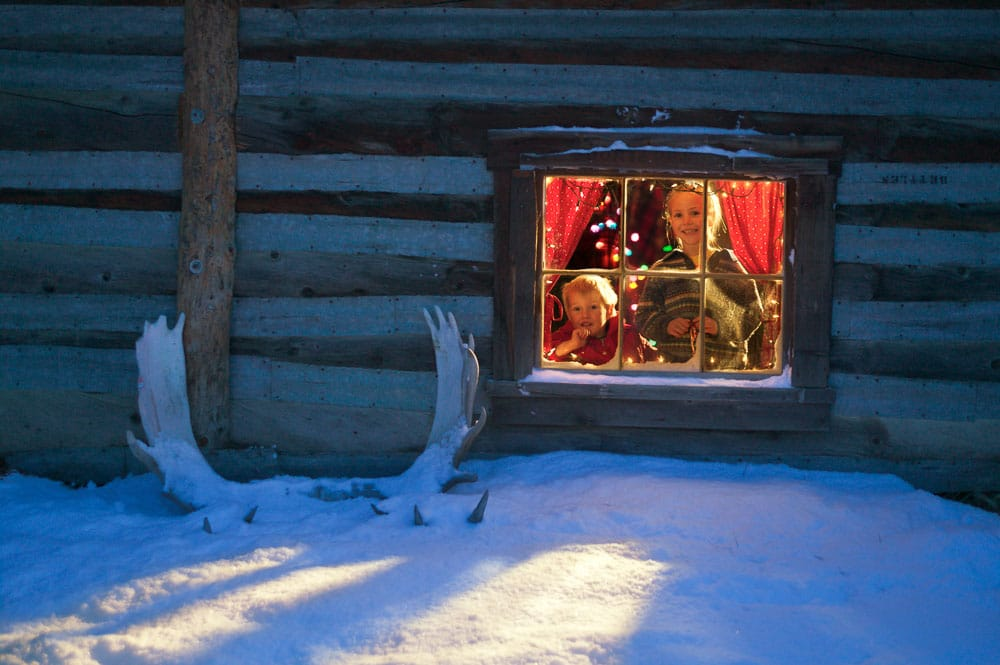 Leo and Julia Hicker peer out of the window of their historic log cabin